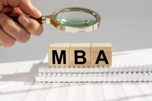 "A magnifying glass over wooden blocks of the letters ""MBA"""